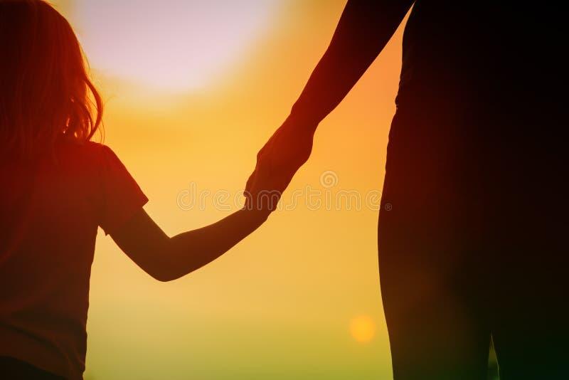 Silhouet van moeder en dochterholdingshanden bij zonsondergang royalty-vrije stock foto