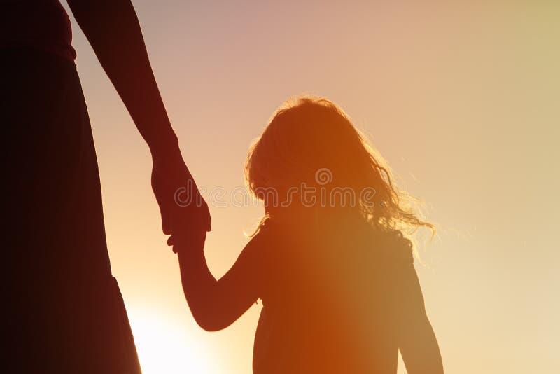 Silhouet van moeder en dochterholdingshanden bij zonsondergang stock foto