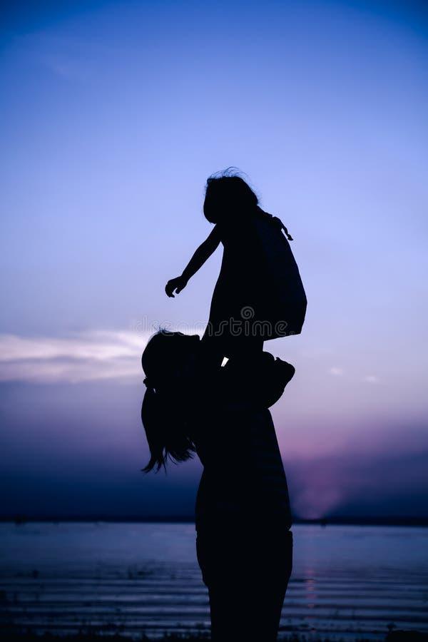 Silhouet van moeder en kind die van de mening genieten bij rivieroever stock afbeeldingen