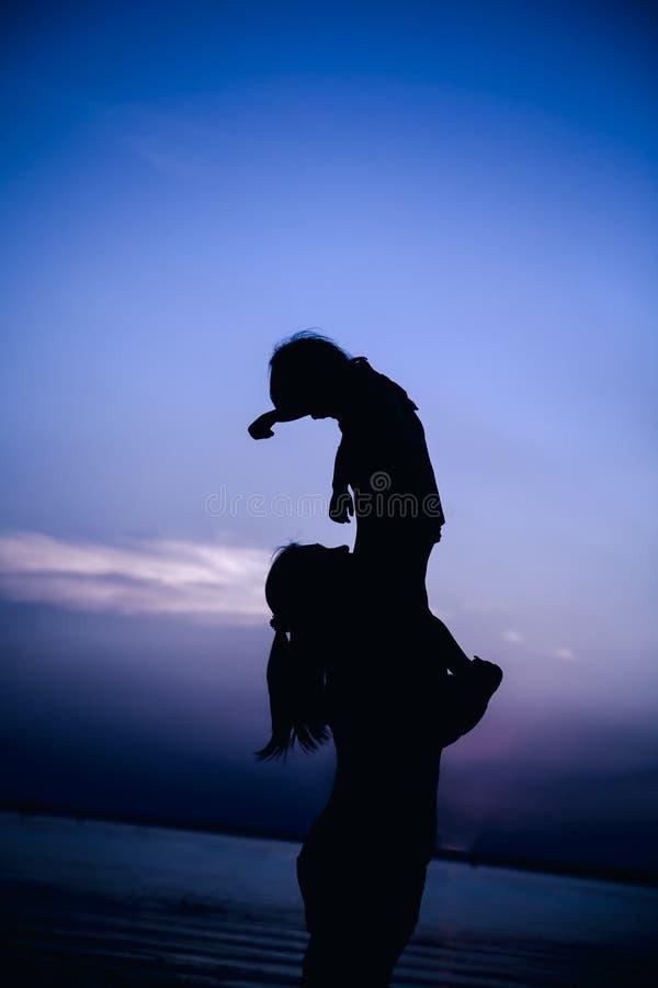 Silhouet van moeder en kind die van de mening genieten bij rivieroever stock afbeelding