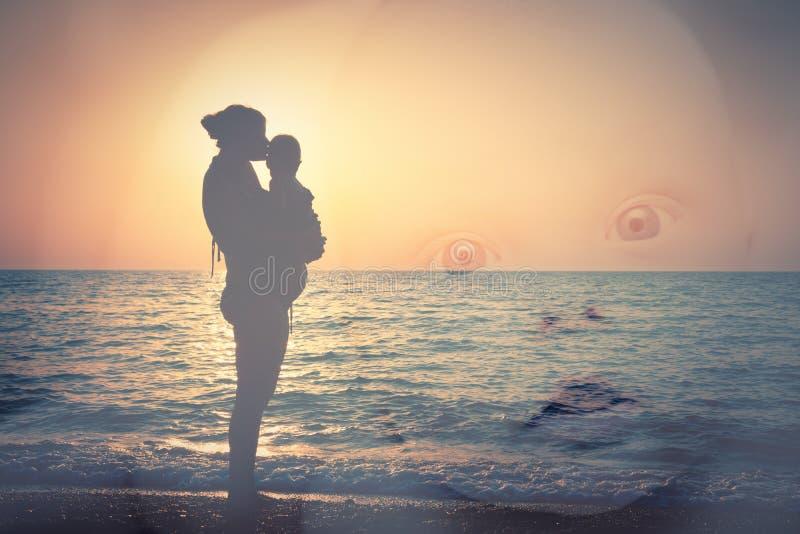 Silhouet van moeder en kind op het strand, en het gezicht van een kind stock foto's