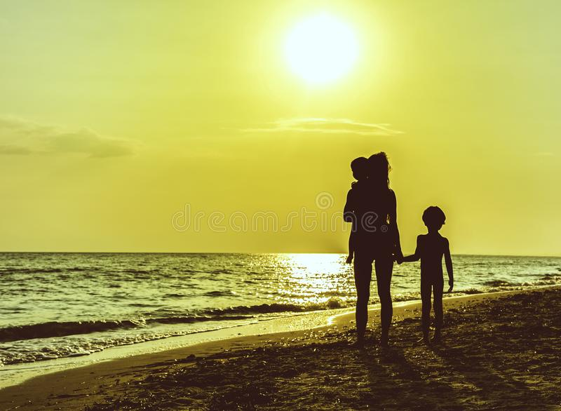 Silhouet van moeder met kinderen op strand in zonsondergang royalty-vrije stock afbeelding