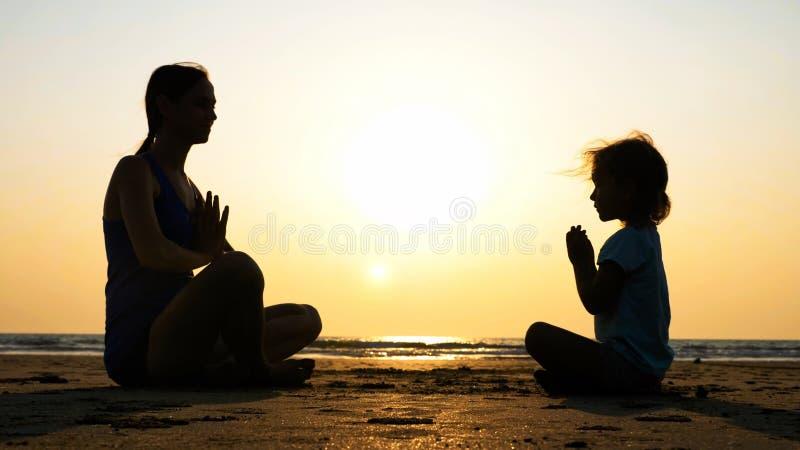 Silhouet van moeder met weinig dochter die samen bij zonsondergang mediteren stock afbeeldingen