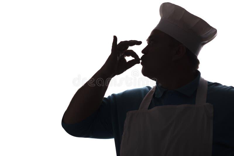 Silhouet van mollige, gelukkige chef-kok het kussen vingers uit heerlijke schotels, het profiel van een persoon in eenvormig tone royalty-vrije stock foto