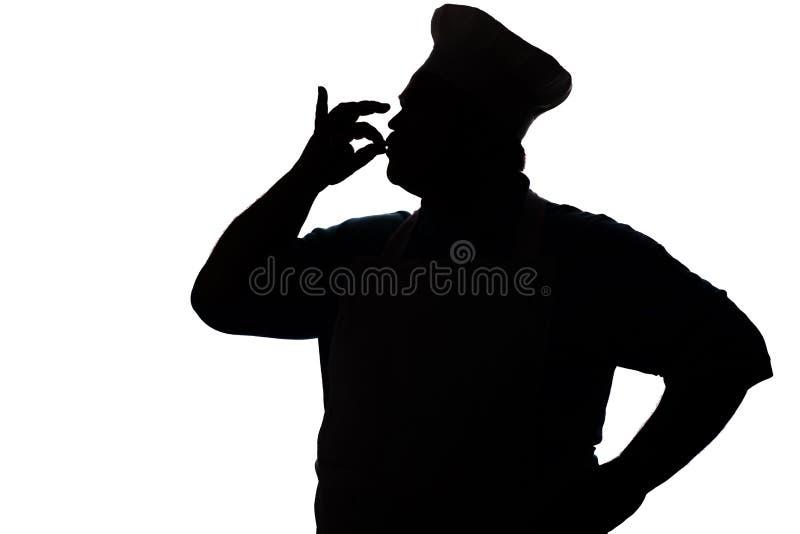Silhouet van mollige, gelukkige chef-kok het kussen vingers uit heerlijke schotels, het profiel van een persoon in een keuken een royalty-vrije stock foto's