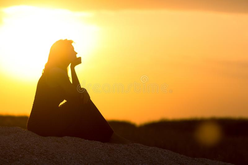 Silhouet van mooie nadenkende meisjeszitting op het zand en het genieten van de van zonsondergang, het cijfer van jonge vrouw op  royalty-vrije stock afbeeldingen