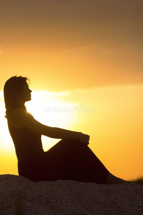 Silhouet van mooie nadenkende meisjeszitting op het zand en het genieten van de van zonsondergang, het cijfer van jonge vrouw op  stock foto