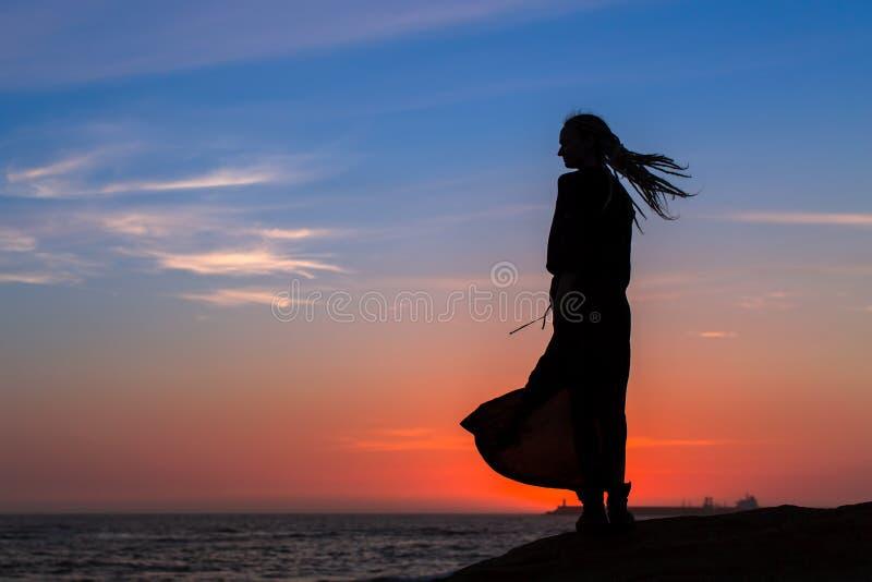 Silhouet van mooie vrouw in kleding op de zeekust stock foto's