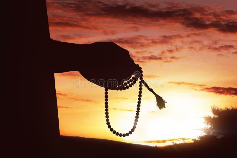 Silhouet van moslimmensenhand die terwijl het houden tasbih bidden royalty-vrije stock afbeelding