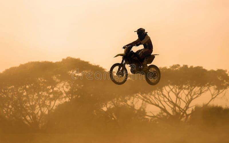 Silhouet van motocrossruiter het springen stock foto's