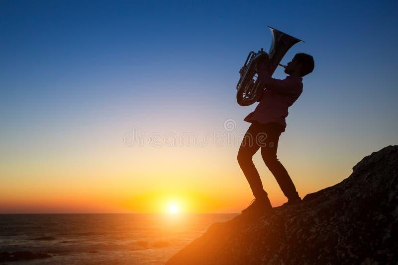 Silhouet van musicus die de trompet op rotsachtige overzeese kust spelen tijdens zonsondergang royalty-vrije stock afbeelding