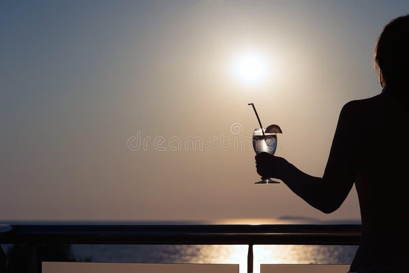 Silhouet van naakt meisje met cocktail in handen op zonsondergangachtergrond royalty-vrije stock fotografie