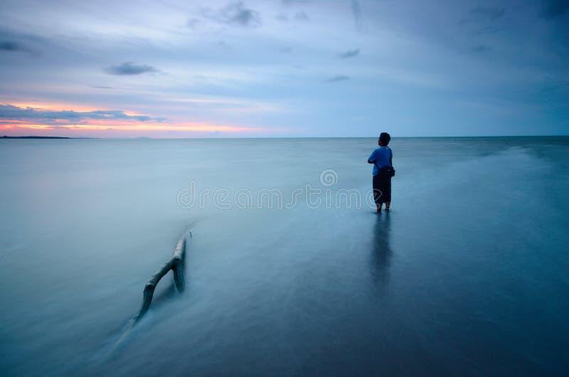 Silhouet van niet geïdentificeerde plaatselijke bevolking bij jubakar strand, tumpat kelantan maleisië stock afbeelding