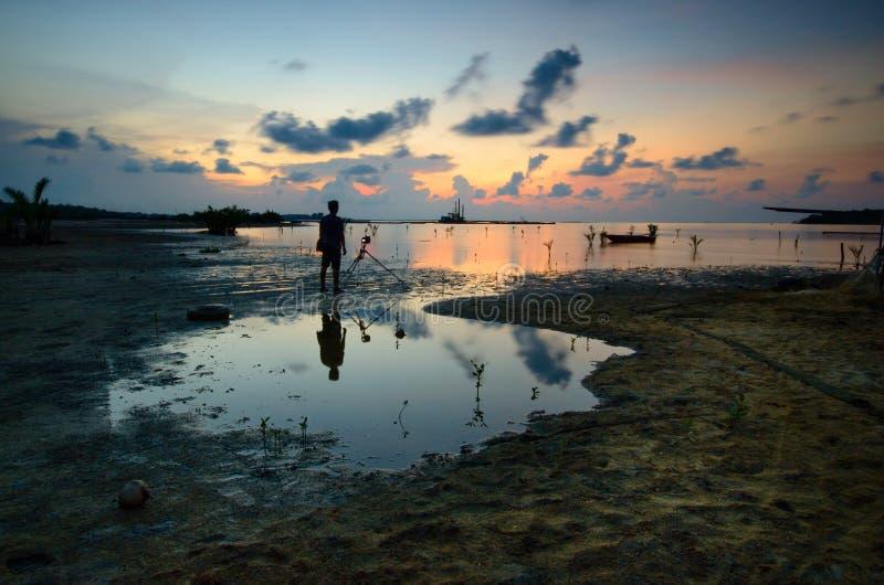 Silhouet van niet geïdentificeerde plaatselijke bevolking bij jubakar strand, tumpat kelantan maleisië royalty-vrije stock fotografie