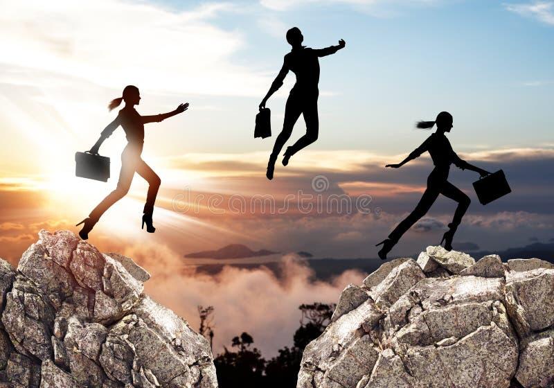 Silhouet van onderneemster die op bergen springen royalty-vrije stock foto's