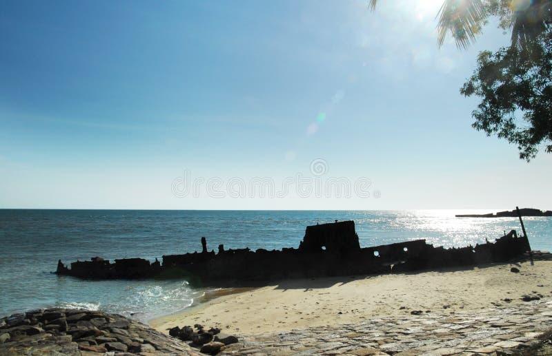 Silhouet van oude vastgelopen verlaten schipbreukzitting op de kust van het strand stock fotografie