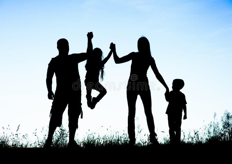 Silhouet van ouders en jong geitje die pret het besteden tijd hebben stock foto's