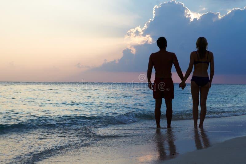Silhouet van Paar die langs Strand bij Zonsondergang lopen royalty-vrije stock fotografie