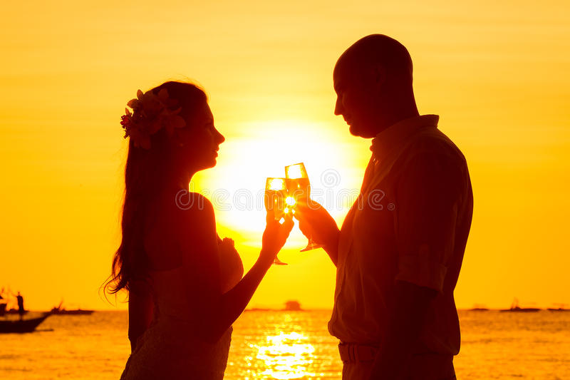 Silhouet van paar die van glas champagne op tropische bea genieten stock afbeelding