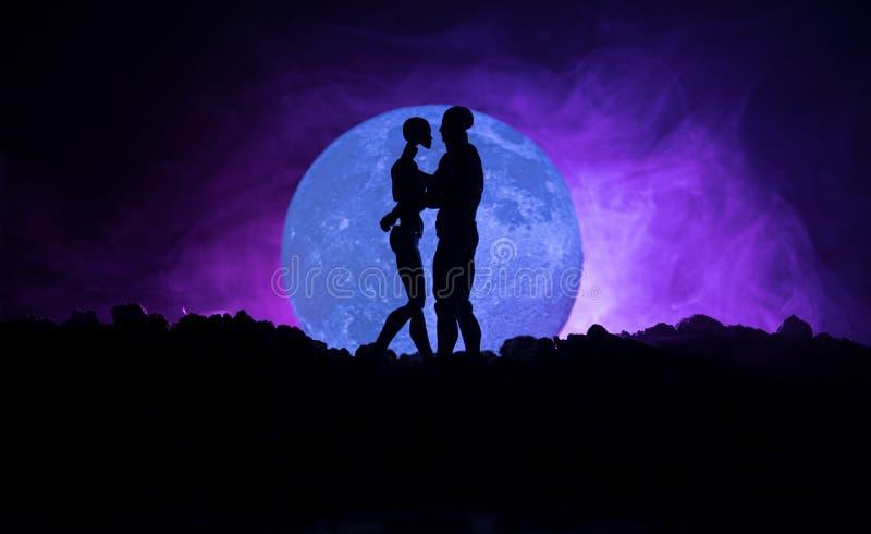 Silhouet van paar het kussen onder volle maan Het meisjeshand van de kerelkus op de achtergrond van het volle maansilhouet Het co royalty-vrije stock fotografie
