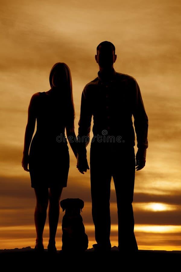 Silhouet van paar met een hond royalty-vrije stock afbeeldingen