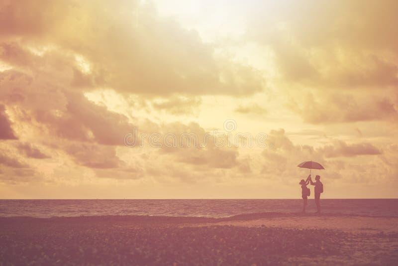 Silhouet van paarmensen of toerist die op het strand zich binnen bevinden royalty-vrije stock afbeeldingen