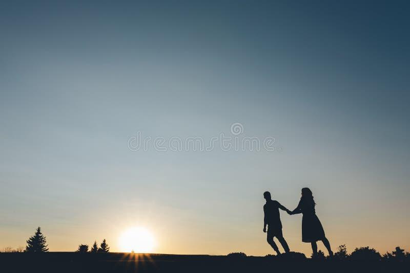 Silhouet van paren die de holdingshanden de heuvel beklimt stock foto
