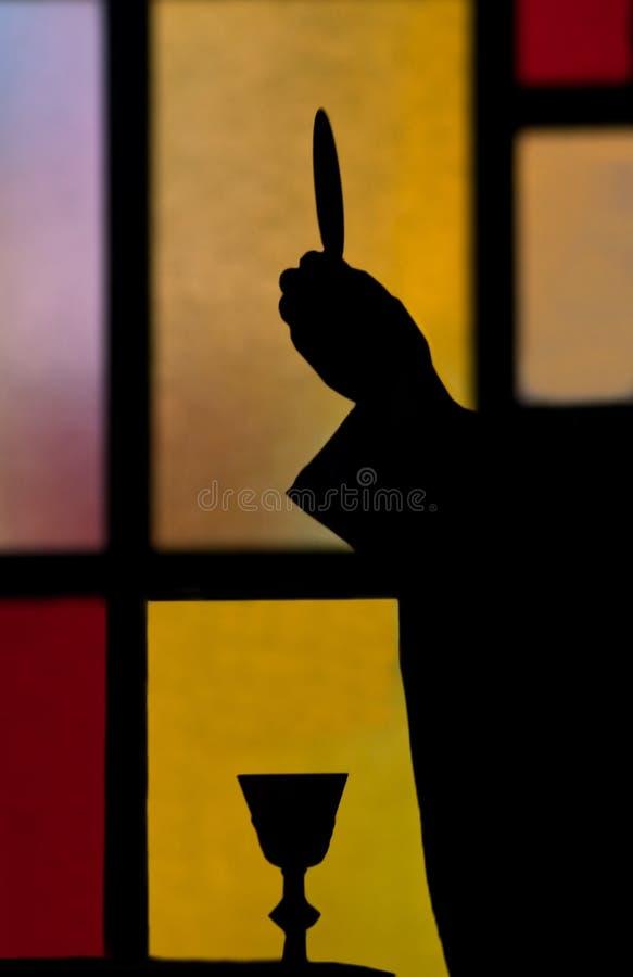 Silhouet van priester opheffende gastheer royalty-vrije stock afbeelding