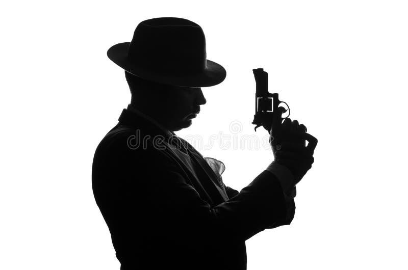 Silhouet van privé-detective met een kanon in rechts De kant van het agentenverblijf aan camera en blikken zoals mafioso Al Capon stock afbeelding