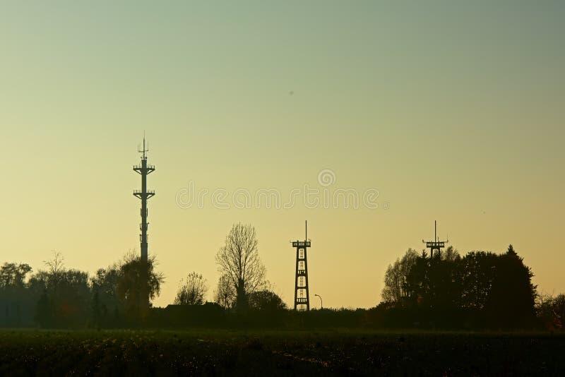 Silhouet van radiotoren en watchtowers van een luchthaven in avondlicht stock foto