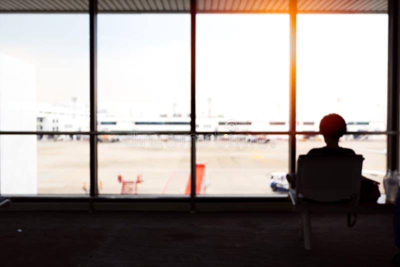 Silhouet van reizende vrouwenzitting op stoel voor windo stock fotografie