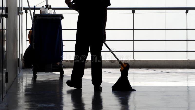 Silhouet van schoonmakende de dienstmensen die vloer vegen royalty-vrije stock foto