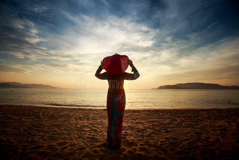 silhouet van slank meisje in lang en hoed in zonsopgang over overzees stock fotografie