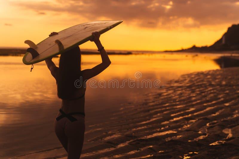 Silhouet van slank meisje met surfplank in handen bij strand op achtergrond van mooie zonsondergang royalty-vrije stock foto
