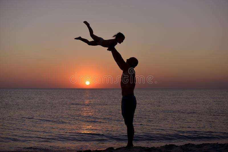 Silhouet van speelpapa en dochter op de achtergrond van de overzeese zonsondergang stock fotografie