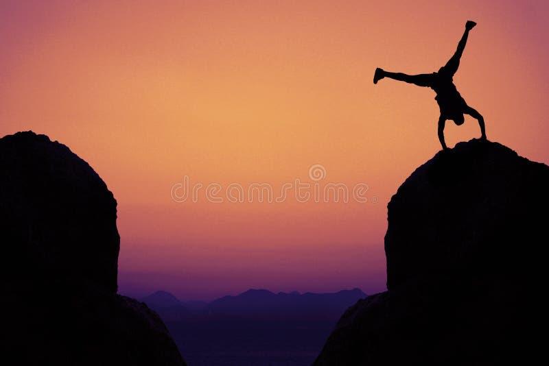 Silhouet van sportieve turner in bergen als symbool voor pret stock afbeelding