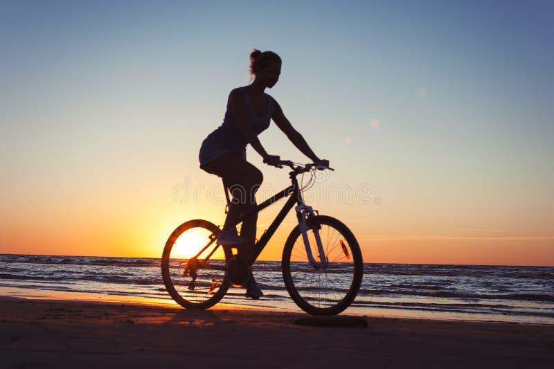 Silhouet van sportieve vrouwen berijdende fiets op multicolored zonsondergangachtergrond royalty-vrije stock foto's