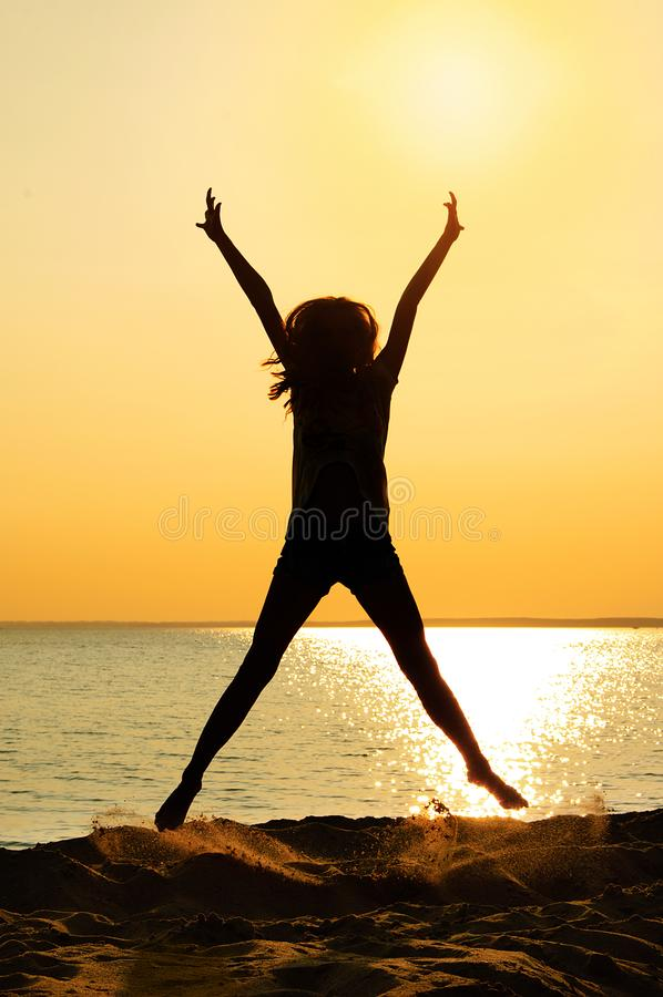 Silhouet van springend meisje De zomer op het strand bij zonsondergang royalty-vrije stock foto