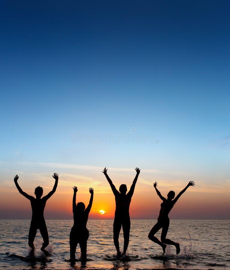 Silhouet van springende mensen stock foto's