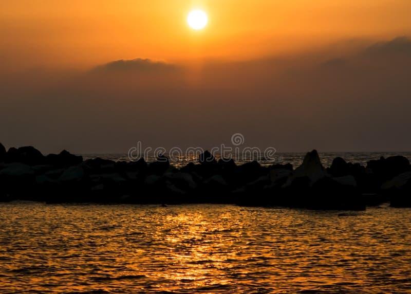 Silhouet van steenkust op een achtergrond van overzeese zonsondergang Kustlijn in de avond stock foto's