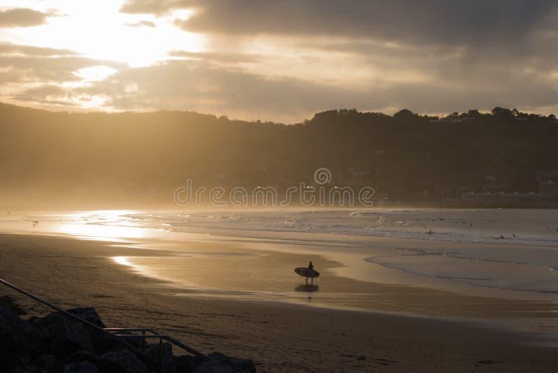 Silhouet van surfers in toneel gouden zonsondergang op hendayestrand, Baskisch land, Frankrijk stock afbeeldingen