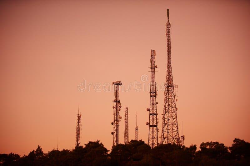 Silhouet van telecommunicatietoren op zonsonderganghemel stock afbeeldingen
