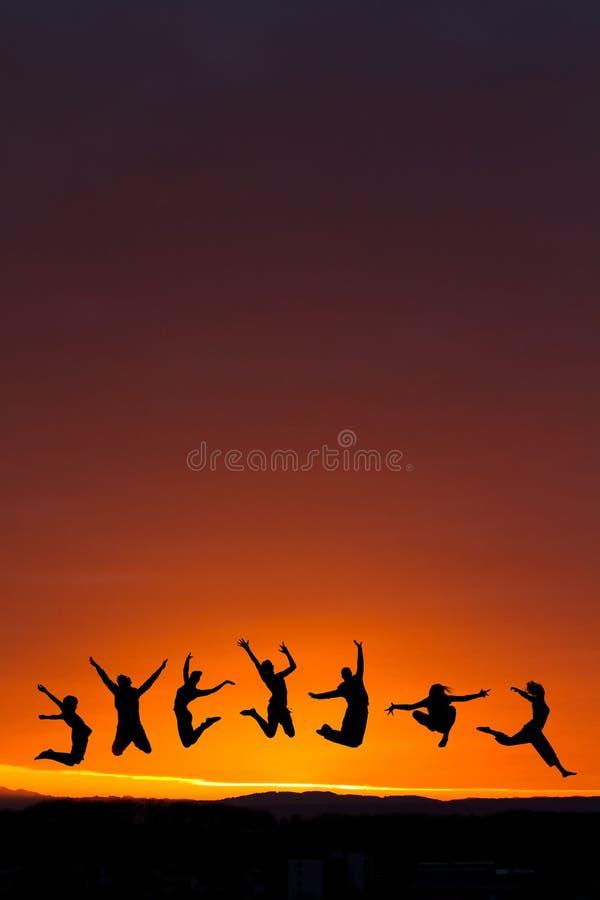 Silhouet van tieners die in zonsondergang springen stock foto's