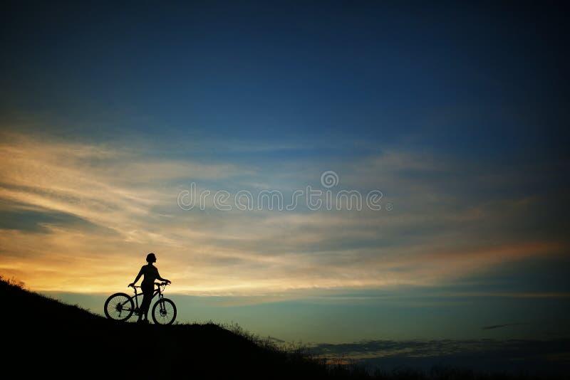 Silhouet van toerist en fiets op hemelachtergrond stock foto