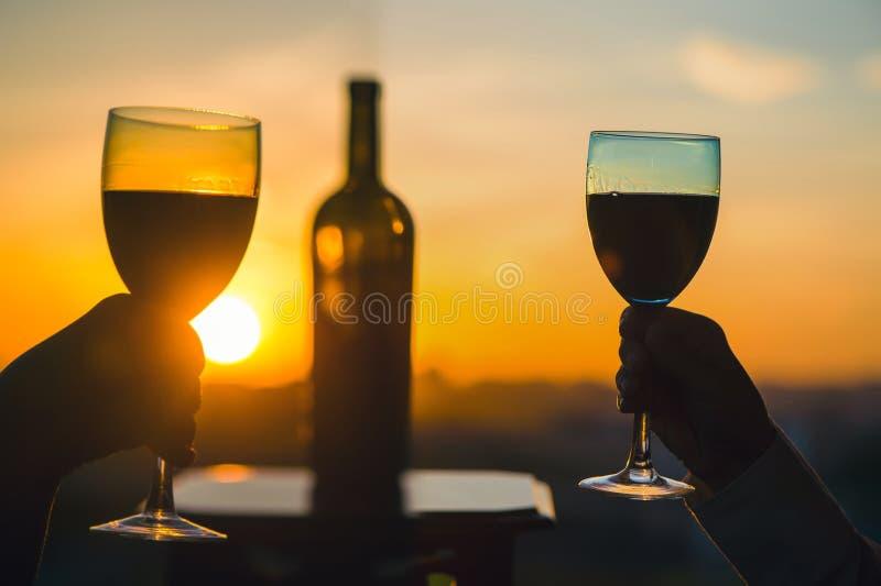Silhouet van twee handen die wijn op zonsondergangachtergrond roosteren stock foto's