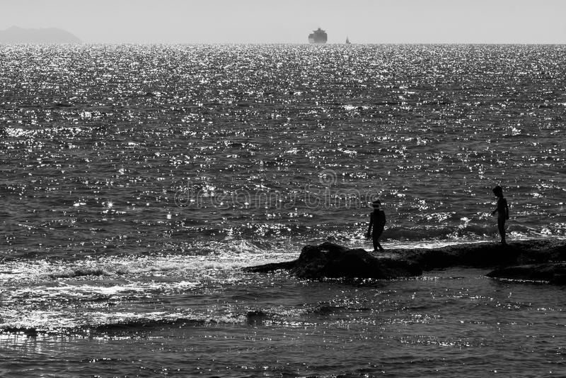 Silhouet van Twee Kinderen die op Ertsader dichtbij Overzees bij Zonsondergang spelen royalty-vrije stock foto