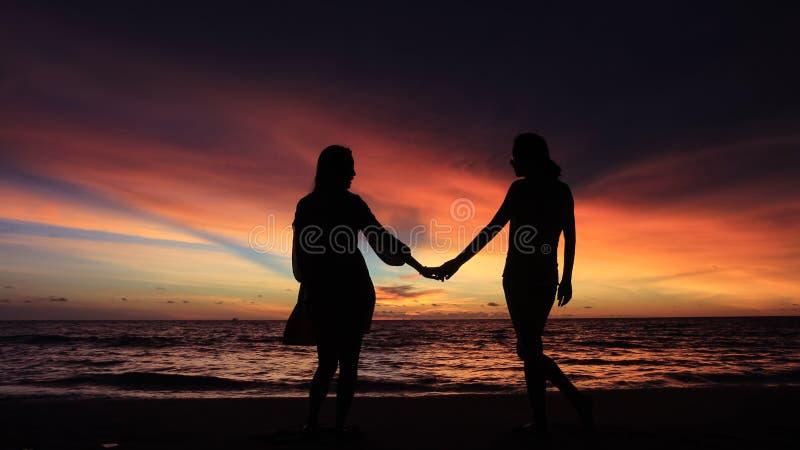 Silhouet van twee meisjes die handen samen op strand houden royalty-vrije stock foto