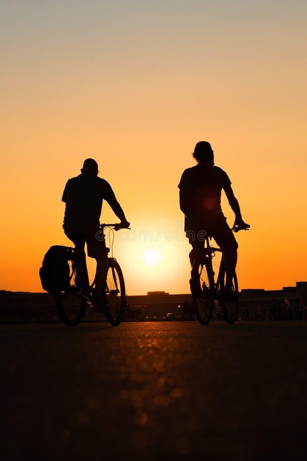 Silhouet van twee mensen die fiets met backgrou van de zonsonderganghemel berijden royalty-vrije stock foto's
