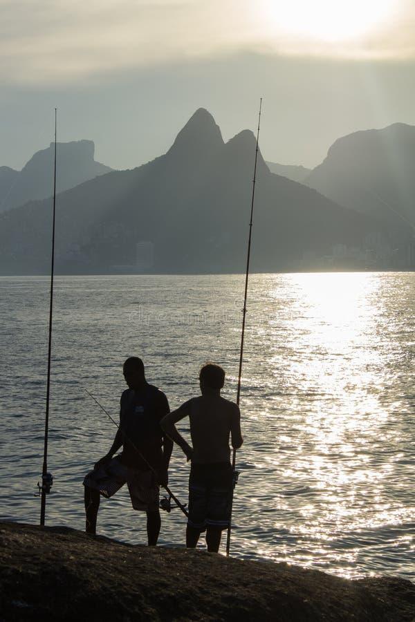 Silhouet van twee vissers bij zonsondergang op de stenen van het strand van Arpoador in de stad van Rio de Janeiro Brazil stock foto