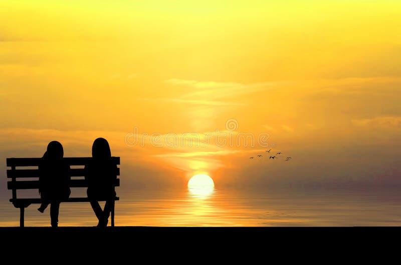 Silhouet van twee vrienden die op houten bank dichtbij strand zitten stock foto
